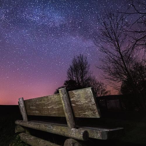 Eine Bank steht in der Nacht auf einem Feld. Im Hintergrund ist ein Himmel mit Milchstrasse zu sehen. Das Foto entstand bei einem Fotoworkshop zur Nachtfotografie in Hohenfelden bei Erfurt.