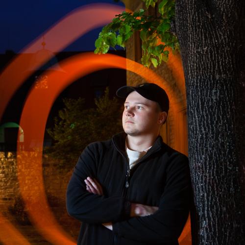 Anlässlich eines Fotoworkshops zur Nachtfotografie lehnt sich ein Mann in der Nacht an einen Baum. Der Mann ist mit einem Blitzlicht aufgehellt und hinter dem Mann sind bunte Leuchtstreifen zu sehen.