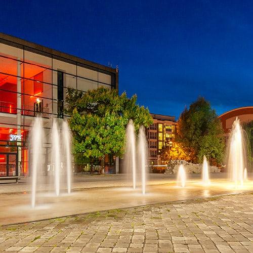 Vor dem erleuchteten Opernhaus in Erfurt sind in der Nacht Springbrunnen aktiv und angeleuchtet. Das Foto entstand bei einem Fotoworkshop Nachtfotografie.